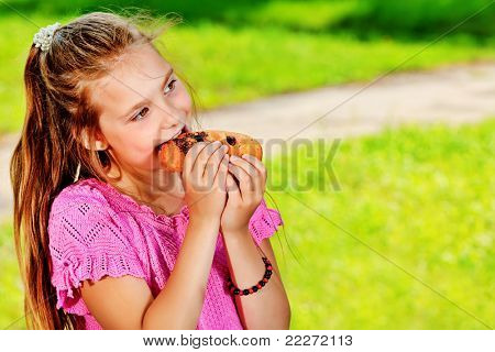 A girl is eating her hot dog outdoors.