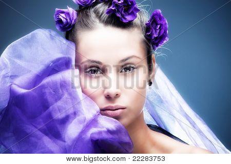 gentle young woman beauty portrait with purple flowers in hair, studio shot