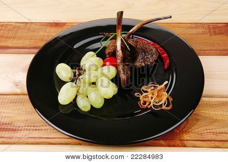 grilled ribs on black plate over wood