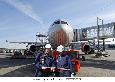 two air mechanics, engineers, with large airliner in background, airport ground activities