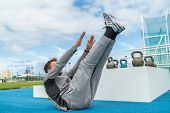 Abs exercise leg lift toe touch sit-up workout man strength training at fitness gym athletic stadium poster