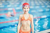 Cute little girl in swimsuit, swim-cap and goggles standing by swimming-pool poster