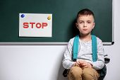 Little boy being bullied at school near chalkboard with sign STOP indoors poster