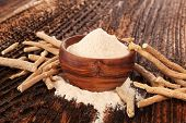 Heap Of Ashwagandha Powder In Wooden Bowl  With Roots. Superfood Remedy. poster