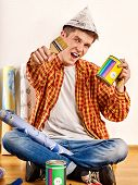 Repair home man holding paint roller for wallpaper. Happy mad male in newspaper cap renovation apart poster