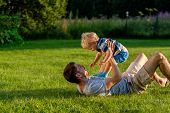 Happy man and child having fun outdoor on meadow.  Family lifestyle scene of father and son resting  poster