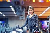 fitness, sport, exercising, weightlifting and people concept - smiling young woman choosing dumbbell poster