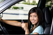 image of 16 year old  - a 16 year old girl sitting in her new car as she holds her key and smiles - JPG