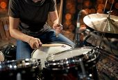music, people, musical instruments and entertainment concept - male musician with drumsticks playing poster