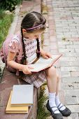 image of bagpack  - Young school girl with pink bagpack sits reading the book - JPG