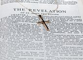 picture of revelation  - Old fashioned gold cross and chain laying on a page from the bible on the revelation - JPG