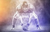 American football player starting football game on big modern american football field with lights an poster