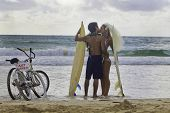 picture of kissing couple  - newlywed couple kissing at the beach with surfboards and bikes in hawaii - JPG