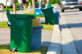 stock photo of recycle bin  - Green and blue recycling bins by the curb on a residential street - JPG