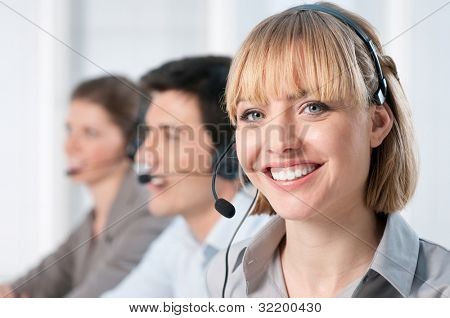Smiling lady working at call center office with colleagues
