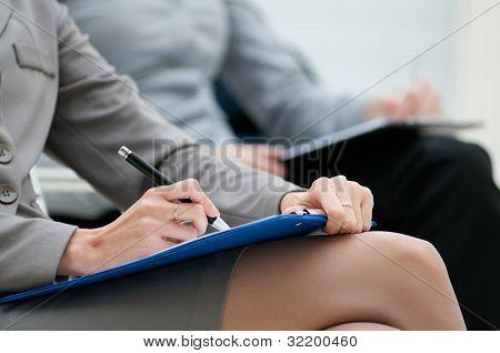 Geschäftsfrau, die während eines Treffens, Closeup auf Merkzettel schreiben