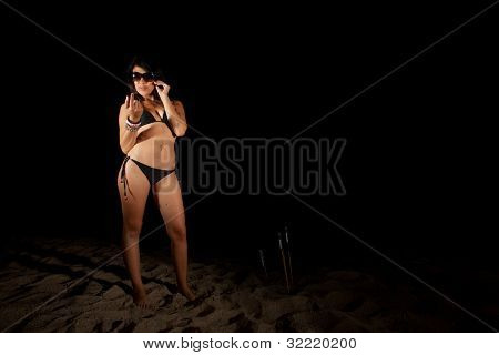 Young Woman On Beach At Night With Bottle Rockets