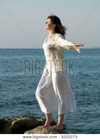 Young Barefoot Lady Stays On Stone Arms Outstretched
