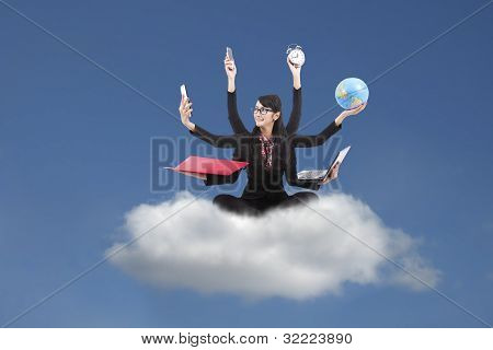 Multi-tasking Business Woman Sitting On a Cloud