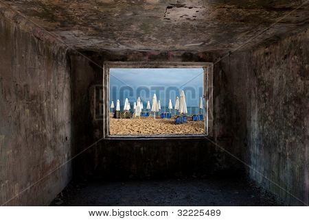 Dark old room with window with beach and sea behind him