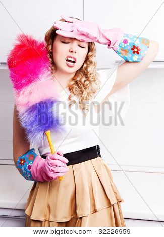 beautiful tired young housewife wearing rubber gloves and holding a dust brush in the kitchen at home