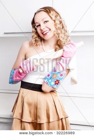 beautiful young housewife wearing rubber gloves and holding a rolling pin in the kitchen at home