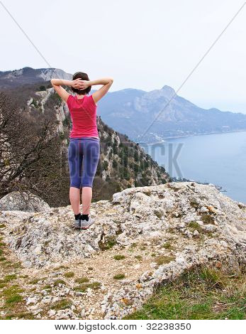 Girl  standing on precipice above sea