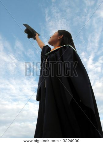 Female Graduate Raises Mortarboard To Sky