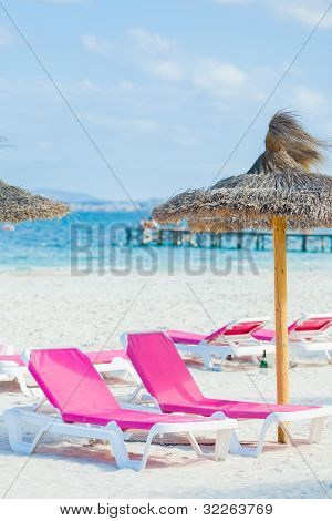 Two chairs and umbrella on the beach.