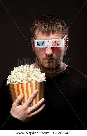 Portrait of serious man watching 3D movie and holding bucket of popcorn