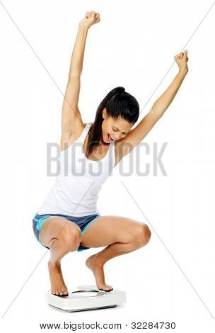 portrait of an excited hispanic woman on a scale who has lost weight and is fit and healthy