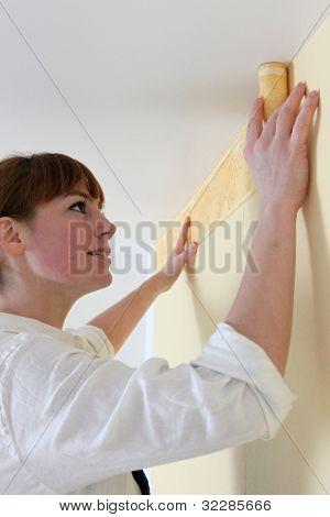 handywoman laying frieze in bedroom
