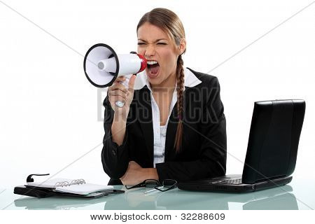 businesswoman shouting angrily with loudspeaker and laptop