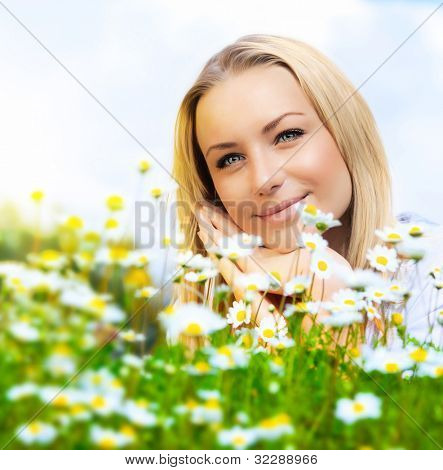 Beautiful woman enjoying daisy field and blue sky, nice female lying down in the meadow of flowers, pretty girl relaxing outdoor, happy young lady and green spring nature in harmony