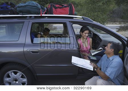 Man examining map by his family minivan