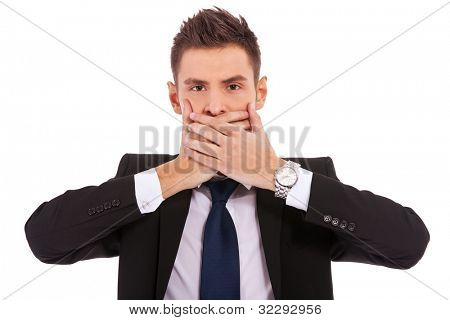 business man making the speak no evil gesture over white . young businessman covering his mouth with his hand