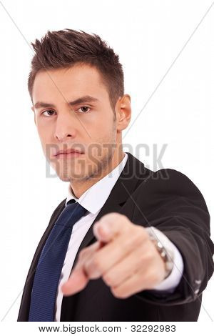 Young business man in a suit pointing and accusing you, on white background