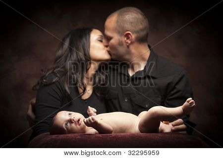 Mixed Race Couple Kiss While Baby Lays on Pillow on a Dark Background.