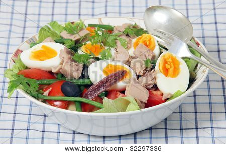 A serving bowl with spoon and fork of traditional nicoise salad - lettuce, potato, tomato, green beans, tuna, anchovies, boiled eggs, capers and black olives, garnished with flat-leaf parsley