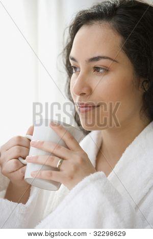 Hispanic woman in a bathrobe drinking coffee