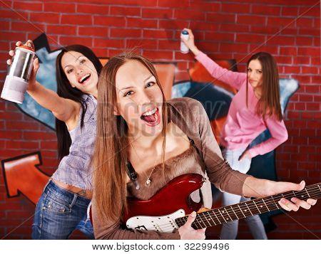 Group people playing guitar against graffiti brick wall.
