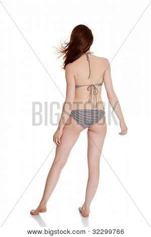 Back view of beauty summer woman in bikini with wind in her hairs, isolated in studio.