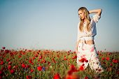 stock photo of red hair  - Beautiful young woman staying in field of flowers in sunny summer day - JPG
