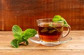 Tea With Mint In A Glass Cup. In A Cup And On A Table Mint Leaves. poster