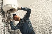 Plumber Installing Electric Heating Boiler. Young Handyman In Uniform Setting Up Electric Heating Bo poster