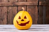 Funny Halloween Pumpkin On Wooden Background. Traditional Halloween Pumpkin With Smiling Face. Hallo poster
