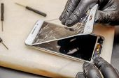 Technician Or Engineer Opening Broken Smartphone For Repair Or Replace New Part On Desk poster