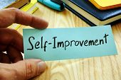 Hand Holds Piece Of Paper With Sign Self Improvement. poster