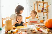 Family Mother And Child Daughter In Hat Witch Are Preparing For Halloween Carve A Pumpkin And Decora poster