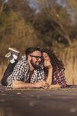 Couple Having Fun On A Lake Docks Picnic, Lying On A Picnic Blanket And Enjoying Beautiful Autumn Da poster